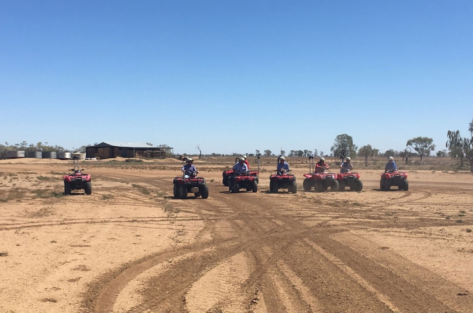 Farmers riding quads in bare paddock